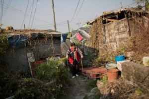 Luo In-soon walks to her Guryong Village home. In 2011, residents received temporary residency cards so they could vote for the first time. Photograph: Lam Yik Fei/Getty Images