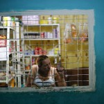 A woman looks out of a window at her shop in a corridor inside the