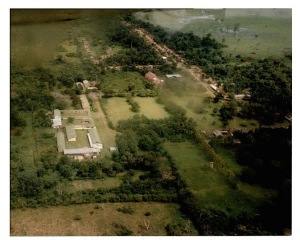 Aerial photograph of Bamanya, in the 1990s. The buildings of the Sisters of the Precious Blood are to the bottom left, the church and parish hall are in the centre, with the village above. To the right, under the river (a tributary of the Ruki), is the former boys' boarding school with the residences of the Fathers a little further down on the left, where the building of the Aequatoria research centre is also situated, hidden from sight by the trees. MSC Borgerhout Collection.